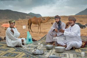 Dhofar, Oman - September 27, 2013: Three men are having a chat in front of theit tent near Salalah in Oman (Dhofar region), Tea and camel milk is available. A camel is standing in the background.