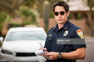 A mid-adult caucasian male police officer stands in front of a car, writing a ticket for a moving violation.